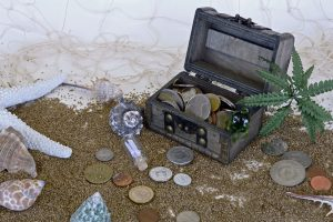 Box of coins on beach with shells
